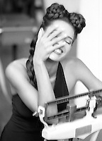 Stock Photo of a Woman in her little black dress standing on a doctor's scale, laughing with her hand in her face.