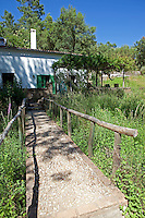 A stone path with rustic wooden handrails leads up to the cottage