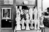 Bosnia. Medjugorje. Statues of the Virgin Mary and Jesus Christ are on sale in a tourist shop. Pictures from the pope John Paul 2 and the italian priest Padre Pio are on display in the window. © 2002 Didier Ruef