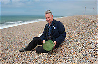 BNPS.co.uk (01202 558833)<br /> Pic: PhilYeomans/BNPS<br /> <br /> John Dadds of the RSPB with one of his insulated tern nests'.<br /> <br /> Terned out nice again...<br /> <br /> Enterprising RSPB warden John Dadds has come to the rescue of one of Britains most exposed colonies of Little terns - thanks to an inspirational trip to a DIY store and a &pound;1.75 hanging basket liner.<br /> <br /> Dadds study of the tiny colony on Chesil beach in Dorset last year had revealed that many of the birds eggs were failing to hatch, and he realised that the wind whistling through the gaps in the pebbles was cooling the eggs down to a critical level.<br /> <br /> After a visit to his local Wilkinson's and armed with a bucket of sand and 12 hanging basket liners, Dadds set to work this year to provide a more draught proof nest for the returning birds. <br /> <br /> So far 21 pairs have taken up the nests and Dadds is mounting a round the clock watch over them to see if his plan has worked.