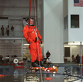 United States Senator John H. Glenn Jr. (Democrat of Ohio), STS-95 payload specialist, simulates a parachute drop into water during emergency bailout training at the Sonny Carter Training Center on October 8, 1998. Other STS-95 crew members are seen deploying or using life rafts in the Neutral Buoyancy Laboratory's pool in the background. .Credit: NASA via CNP