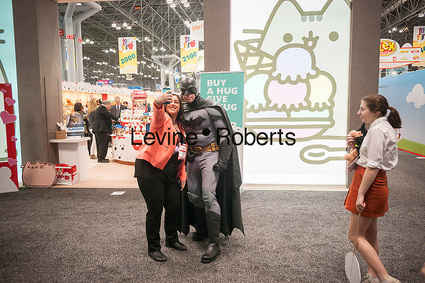 An actor dressed as Batman poses for selfies as he promotes the Batman themed plush at the Gund booth at the114th North American International Toy Fair in the Jacob Javits Convention center in New York on Sunday, February 19, 2017.  The four day trade show with over 1000 exhibitors connects buyers and sellers and draws tens of thousands of attendees.  The toy industry generates over $26 billion in the U.S. alone and Toy Fair is the largest toy trade show in the Western Hemisphere. (© Richard B. Levine)