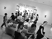 Japanese tourists rest outside the Louis Vuitton designer brand goods store in the 'DFS Galeria' duty free shopping mall store in Tumon, Guam, on Sunday, Mar. 11, 2007.  Sometimes known as 'America in Asia', Guam is a popular destination for Japanese tourists ( accounting for approx 90% of the island's visitors) with average visitor numbers from Japan approaching 1million.  The island, a 3.5 hour flight from Japan, has more than 20 large hotels and numerous duty-free shopping malls catering to the Japanese tourists predilection for designer brand name goods, as well as golfing and other water based entertainment features. In 2007-2008 US military personal currently stationed in the Japanese Okinawan Islands will relocate their bases and operations  to Guam, helping to stabilise the island's economy which suffered after tourism decreased in recent years due to a  fear of flying by Japanese post 9-11 World Trade Centre disaster, a 2003 typhoon and the SARS disease outbreak in Asia.