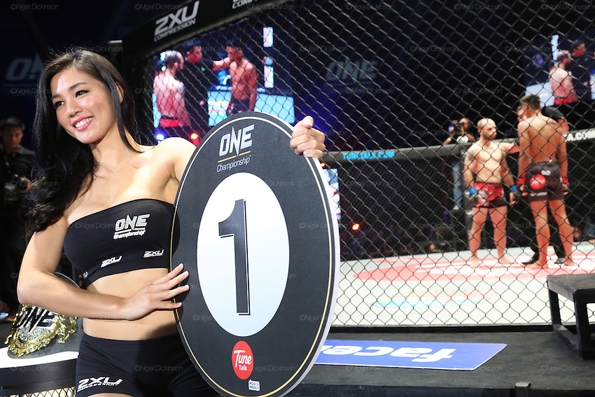 Ring girl walks around the cage announcing first round. Fight between Florian Garel, Zendokai Karate Champion and Keanu Subba, MIMMA Featherweight Champion.<br /><br />MMA. Mixed Martial Arts &quot;Tigers of Asia&quot; cage fighting competition. Top professional male and female fighters from across Asia, Russia, Australia, Malaysia, Japan and the Philippines come together to fight. This tournament takes place in front of a ten thousand strong crowd of supporters in Pelaing Stadium. Kuala Lumpur, Malaysia. October 2015