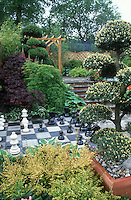 Games in the garden - giant ornamental chess set and board, trees, shrubs, tiered patio, landscaping, fence, Japanese maples, sky