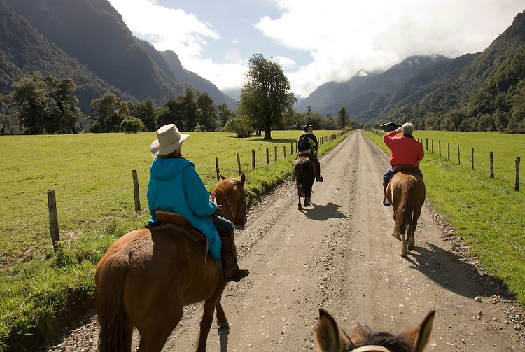 Chile, Lake Country: People riding horses at Peulla in a meadow in the Andes..Photo #: ch616-33271..Photo copyright Lee Foster www.fostertravel.com, lee@fostertravel.com, 510-549-2202.