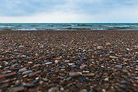 Countless pebbles on an otherwise sandy beach at Warren Dunes State Park at Lake Michigan.