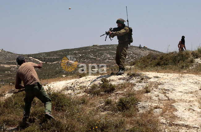 A Palestinian villager from Oref village throws stones at an Israeli police officer during clashes with Jewish settlers after Israeli settlers attacked villages near Nablus City 30 April 2013. Reports state that the clashes occured after an Israeli settler was stabbed to death by a Palestinian man. Israeli media reported that the Palestinian attacker took the settlers' weapon and began firing at a nearby Israeli border guard force, who returned fire, wounding the attacker. Photo by Nedal Eshtayah