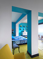 Vibrant colour punctuates the design of every bedroom, this one echoing the azure blue of the sea and the yellow of the shore