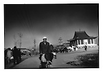 Hui Muslim man rides past mosque which is built in the Chinese temple style, near Linxia, China.  Islam arrived here via Persian traders traveling along the Silk Road, which came through Linxia.