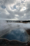 The sun tries to peak out over a blue pool at Geysir, the geothermal field to the east of Reykjavik in South-West Iceland