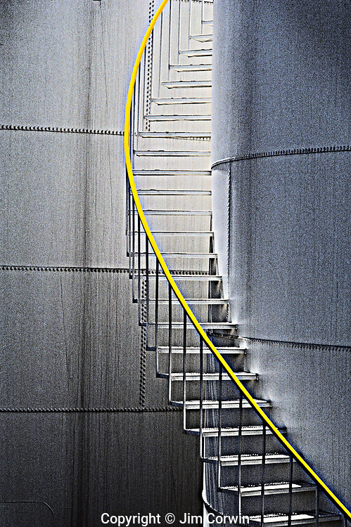 Steps with yellow rail going up out of site along the side of a storage/holding tank in an industrial area of Seattle, Washington State USA