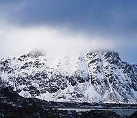 Winter storm clouds cover snow covered summit of Justadtind with village of Stamsund in foreground, Vestvågøy, Lofoten islands, Norway