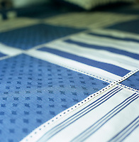 Detail of the bold geometric pattern of a blue and white patchwork bedspread