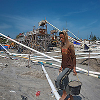 Indonesia - Bangka Island - Sungai Liat - A miner walking carrying sand mixed with tin. It hosts hundreds of workers, from suckers to washers to tin scrappers. The previous night, a worked who had worked all night was carrying two sacks of tin. Police took it when he was coming out of the mine. Sometimes, all the workers are arrested and jailed, and only the owner of the pontoon can redeem them, if he has enough money.