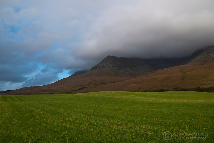 Green field at the base of the Cullin Hills, Isle of Skye, Scotland.  The Cullin Hills, a true paradise for climbers and hill walkers, is probably one of the most recognizable features of Skye. Due to their altitude, the Cullins often trap clouds coming in from the Atlantic.