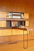 A concealed folding bar pulls out from the wood panelling and is surrounded by shelving hidden behind sliding wood doors