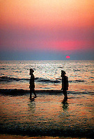 Two Hindu men wading in the waters of the Arabian Sea at Juhu Beach, Mumbai (Bombay), India