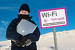 Boy using a laptop computer under a spoof wi-fi sign, Scotland