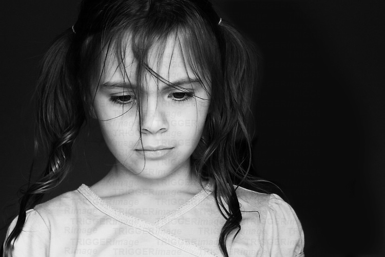 Black and white image of a young girl with her hair in pigtails looking very sad