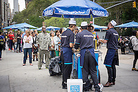 Line of people at the UK bakery chain Greggs' hot dog cart in Madison Square in New York on Tuesday, September 16, 2014, giving away free hot dogs and recording New Yorkers' reactions. The chain is branching out from its sausage rolls and pastries and has introduced coffee and low-fat sandwiches recently. Greggs is the largest bakery chain in the UK with over 1600 outlets. The Madison Square event appeared to have been created solely for the purpose of taping New Yorker's reaction to their hot dogs, perhaps for possible use in a commercial or other advertising. (© Richard B. Levine)