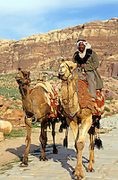 Bedouin riding a camel near the Royal Tombs, Petra, Jordan.