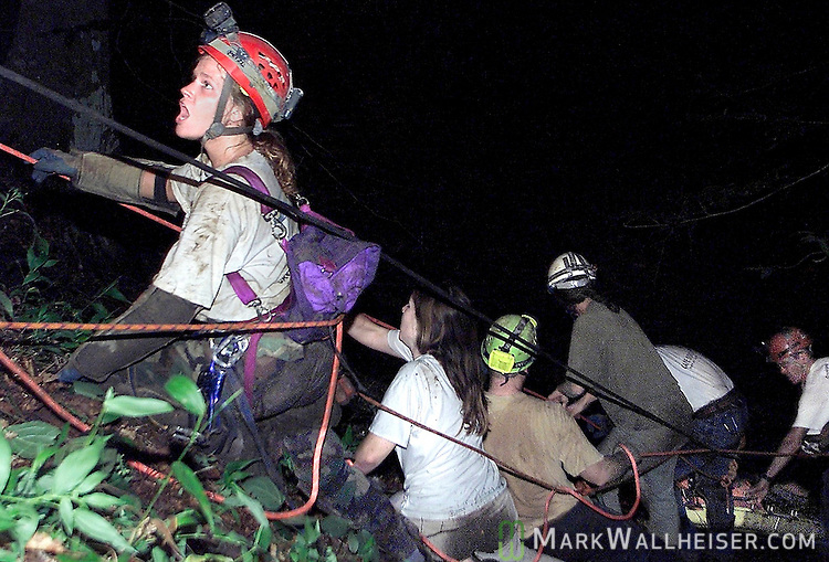 "Tracey Matzke (L), from Largo, yells to the top of the sink for them to ""pull hard"" as her team on the lip of the 60 foot drop into Climax Cave pull and drag the litter carrying the body of 33 year old Bruce Brewer, of Tallahassee  at 4:30 am Monday morning after a 32 + hour rescue effort to recover the spelunker's body."