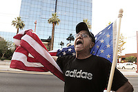 Phoenix, Arizona. June 25, 2012 - Demonstrator Benjamin Campos participated in the protest against the U.S. Supreme Court ruling on Arizona's immigration SB 1070's law. Campos, a Mexican-born man, used an American flag to highlight his U.S. citizenship by naturalization. Immigrant rights groups protested the United States Supreme Court ruling on Arizona law for upholding SB 1070's provision that will allow police to demand papers if there's reasonable suspicion that a person may be illegally in the country. Photo by Eduardo Barraza © 2012