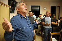 "Italy. Lazio region. Rome. Several men and a few women are praying during the religious service in the baptist church ""Sianta Treime"". The people, all  romanian citizens, are living as immigrants in Italy. Romanian immigration. 28.09.2011 © 2011 Didier Ruef"