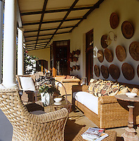 A display of traditional baskets decorates one wall of the veranda which is furnished with a collection of wicker sofas and armchairs
