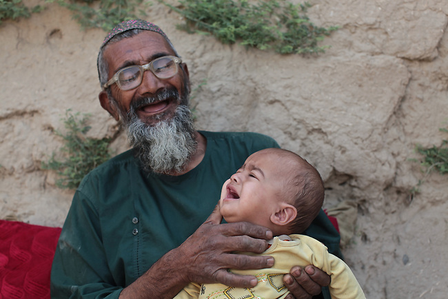 An old man laughs as he holds a crying baby in the village of Deh-e- Chowkay, in the Arghandab valley, near Kandahar, Afghanistan. May 22, 2010. DREW BROWN/STARS AND STRIPES