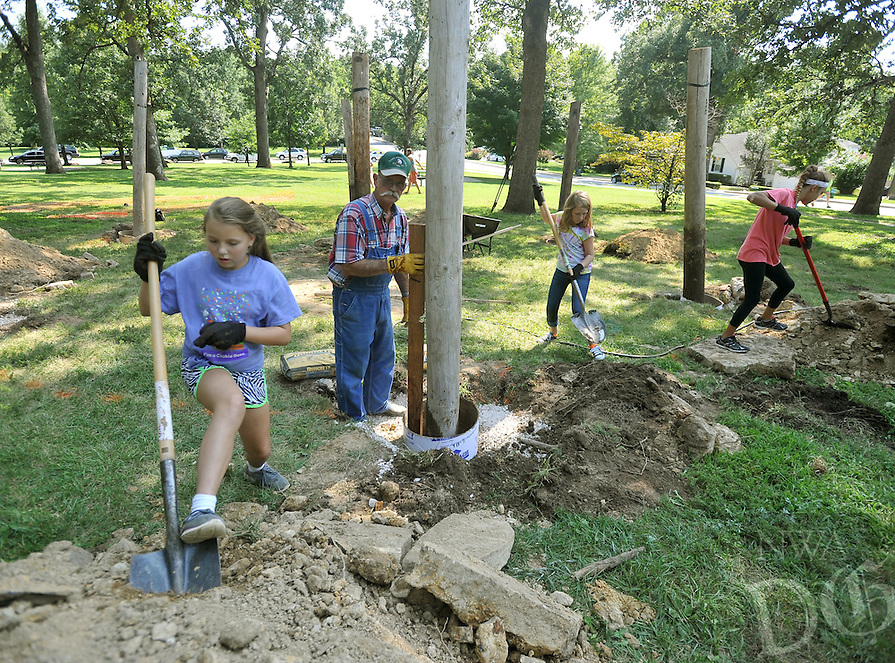 NWA Democrat-Gazette/MICHAEL WOODS &bull; @NWAMICHAELW<br /> Karen Smith, 11, (from left) John Smith, Abigail Lawson, 11, and April Stanley, 11, work on putting the center pole into place Wednesday August 26, 2015, for the new Hammock Hotel installation at Wilson Park in Fayetteville.  Members of Girl Scout Troop 5114 will be installing a &ldquo;hammock hotel&rdquo; on the northwest side of Wilson Park. The project consists of seven, 12-foot-tall posts that will be buried in cement 5 feet underground. Visitors to Wilson Park will be able to hang hammocks and slacklines on the posts without stripping bark from nearby trees. A grand opening for the hammock hotel is scheduled from 10 a.m. to noon Sept. 12.