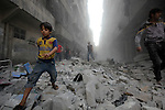 Syrians walk on the rubble of buildings after a missile fired by Syrian government forces hit a residential area in the al-Sukari district in the northern Syrian city of Aleppo on September 15, 2015. Photo by Ameer al-Halbi