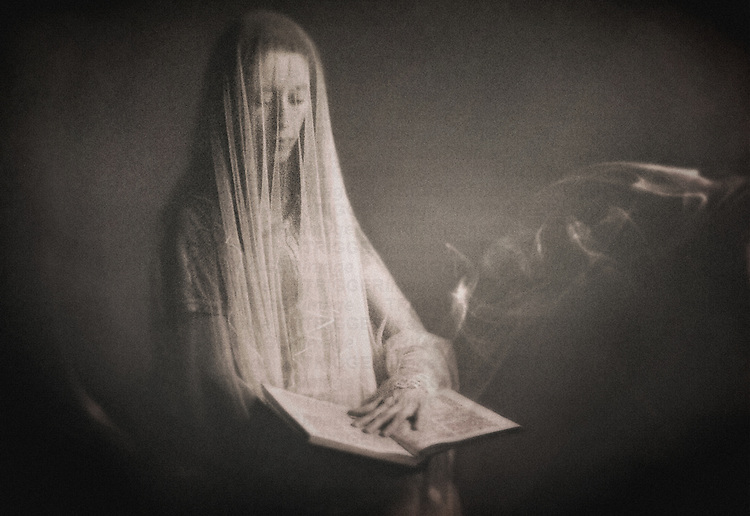 A veiled woman holding a large book with her left hand laying on the pages, and a smoke escaping from it.