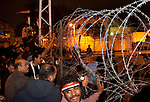 Egyptians outside the heavily guarded Presidential palace in Heliopolis react to news that Egyptian President Hosni Mubarak had stepped down February 11, 2011 following momentous marches on the public buildings across Cairo, Egypt. (Photo by Scott Nelson)