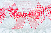 Red and white ribbons tied into bows are used to decorate the stems of the crystal candelabra on the dining table