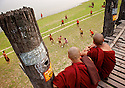 Two monks watch a group of novices playing football from a bridge on the banks of Irrawaddy River near Mandalay.