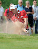 Bradley Dredge of Wales has his eye on the ball as clears it from a sand bunker