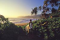 Bodyboarder walking to the beach near sunset