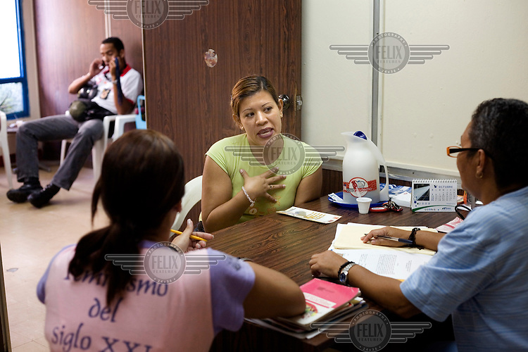 Xiomary Alejandra Quintero Bolivar, a mother of two children, of two and eight years of age, listens to the lawyer Sol Marina Lamon in a session where she has denounced her partner for violence, psychological violence and threats, in the local government offices in the La Vega neighbourhood.