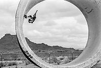 Tony Alva on his skateboard in the California desert. 1976. Photo by John G. Zimmerman