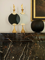 Two contemporary gold and glass ornaments stand on the mantelpiece of a fireplace clad in in Noir Saint Laurent, a French marble.