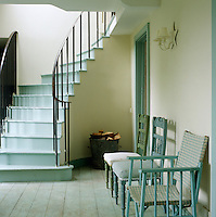 Door frames, stair treads and wooden chairs in this country hallway have all been painted in the same duck-egg blue