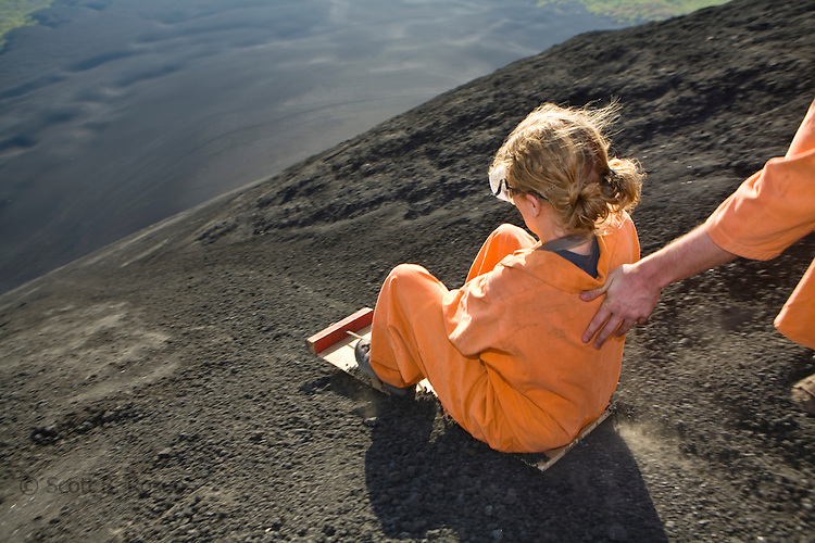 Woman about to be pushed down the active volcano Cerro Negro on her board, Nicaragua