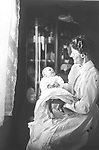 MOTHER AND BABY. Gently lit by the lace-curtained window, this mother and her baby posed for multiple images.<br /> <br /> Photographs taken on black and white glass negatives by African American photographer(s) John Johnson and Earl McWilliams from 1910 to 1925 in Lincoln, Nebraska. Douglas Keister has 280 5x7 glass negatives taken by these photographers. Larger scans available on request.