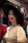 Woman in a vintage dress and a large black straw hat in the Easter Parade on Fifth Avenue in New York City