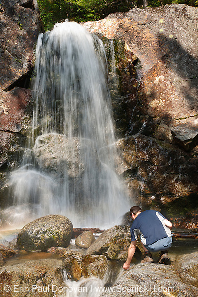 A hiker explores Thirteen Falls along Franconia Brook in the Pemigewasset Wilderness in Franconia, New Hampshire USA.