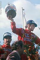 HEUSDEN-ZOLDER - MAY 16: Niki Lauda lifts the winners trophy alongside teammate and second-place finisher Clay Regazzoni after the 1976 Grand Prix of Belgium on May 16, 1976, at the Circuit Zolder near Heusden-Zolder, Belgium.