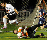 Naperville North goalkeeper Kevin Anderson makes a save with pressure from Libertyville's Austin Bitta during the first half of the teams IHSA boys class 3A semifinal game at North Central College in Naperville Friday, November 5, 2010.  |  Jonathan Miano~Staff photographer