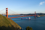 California: Container ship passing under Golden Gate Bridge, view of Golden Gate Bridge and city.  Photo # 3-casanf78411. Photo copyright Lee Foster.